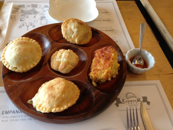 Starting at right and going clockwise:  cheesy chipa, corn and cheese empanada, chicken empanada, beef empanada, and regular chipa in the middle